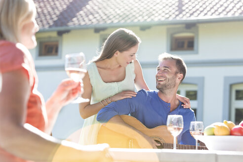 Smiling young couple playing guitar and drinking wine on sunny patio - CAIF12701
