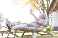 Senior man using digital tablet relaxing on lounge chair in backyard - CAIF12704