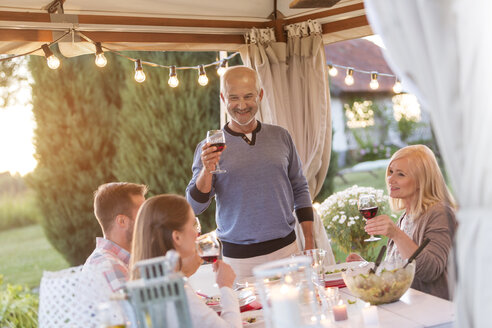 Senior man toasting family with red wine at patio table - CAIF12707