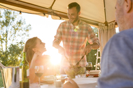 Young man serving salad to wife at sunny patio table - CAIF12716