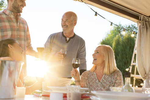 Family drinking wine at sunny patio table - CAIF12719