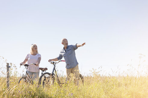 Senior couple bike riding in sunny rural field under blue sky - CAIF12722