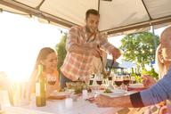 Man serving salad at sunny patio table - CAIF12731
