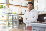 Portrait smiling waiter behind the counter in cafe - CAIF12767
