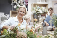Smiling florist arranging bouquet in flower shop - CAIF12794