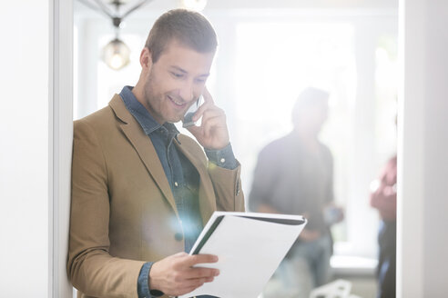 Smiling businessman talking on cell phone and looking down at notebook in office - CAIF12812