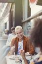 Smiling friends eating dessert at sidewalk cafe - CAIF12833