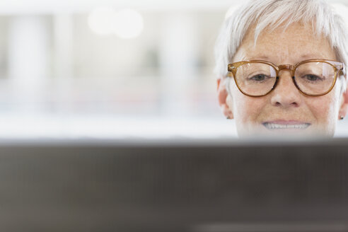 Senior businesswoman with eyeglasses using computer - CAIF12851