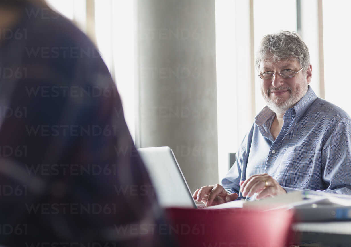 Portrait smiling man working at laptop in adult education classroom - CAIF12854 - Sam Edwards/Westend61