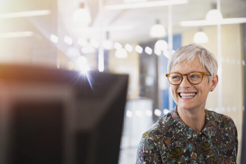 Enthusiastic senior businesswoman looking away in office - CAIF12860