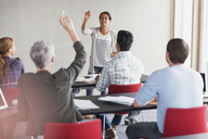 Teacher calling on student with hand raised in adult education classroom - CAIF12869