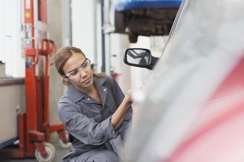 Female mechanic examining car in auto repair shop - CAIF12881