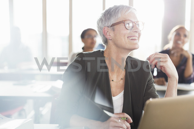 Smiling senior woman at laptop in adult education classroom - CAIF12905