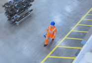 Worker in reflective clothing walking with toolbox in factory - CAIF12953