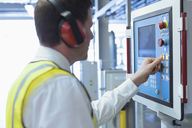 Worker with ear protectors at control panel in machinery - CAIF12971