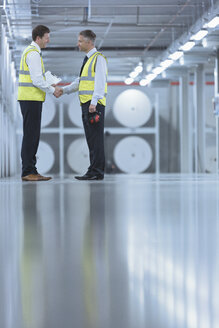 Businessmen in reflective clothing shaking hands in printing plant - CAIF12977