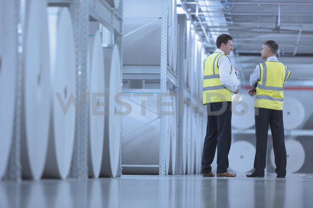 Businessmen in reflective clothing talking near large paper spools in printing plant - CAIF12983