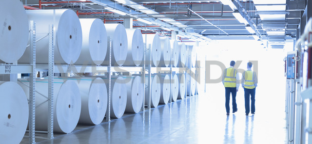 Workers in reflective clothing walking along large paper spools in printing plant - CAIF12989 - Martin Barraud/Westend61