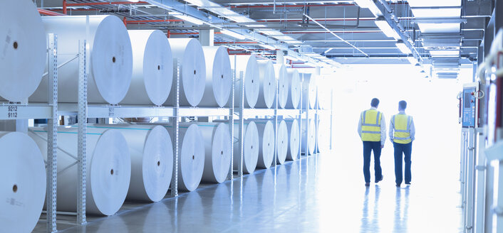 Workers in reflective clothing walking along large paper spools in printing plant - CAIF12989