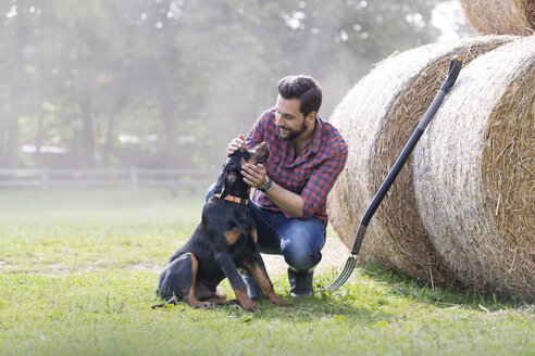 Man petting dog next to rolled hay bales - CAIF13010