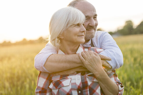 Senior couple hugging in rural wheat field - CAIF13028