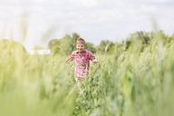 Carefree boy running in sunny rural field - CAIF13043