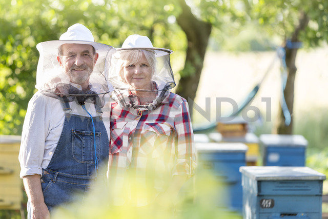 Portrait confident beekeepers in protective hats near hives - CAIF13055