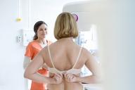 Nurse helping patient prepare for mammogram in examination room - CAIF13070
