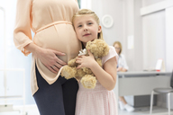 Portrait girl with teddy bear hugging pregnant mother in doctor's office - CAIF13076
