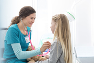 Nurse using stethoscope on girl patient in examination room - CAIF13079