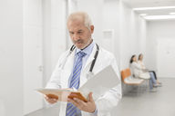 Doctor making rounds reviewing medical record in hospital corridor - CAIF13085