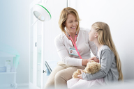 Pediatrician using stethoscope on girl patient in examination room - CAIF13091