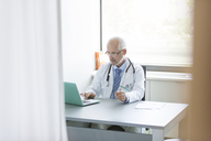 Doctor working at laptop in doctor's office - CAIF13097