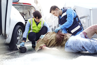 Rescue workers tending to car accident victim in road - CAIF13115