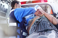 Rescue worker tending to patient at back of ambulance - CAIF13136