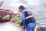 Rescue workers loading car accident victim into back of ambulance - CAIF13145