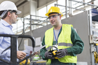 Engineer and worker in protective workwear talking in factory - CAIF13154