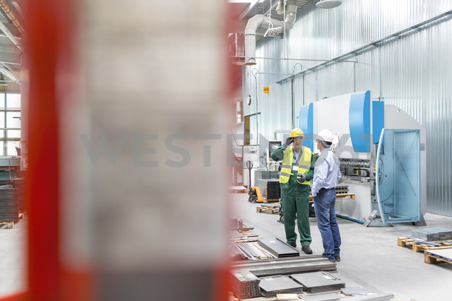 Engineer and worker talking in factory - CAIF13157