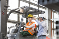 Supervisor directing worker driving forklift in factory - CAIF13160