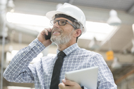 Engineer with hard-hat and digital tablet talking on cell phone - CAIF13172