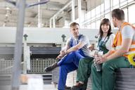 Workers enjoying coffee break in factory - CAIF13178