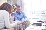 Interior designer using digital tablet in consultation with couple - CAIF13220