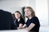 Smiling businesswoman listening in meeting - CAIF13277
