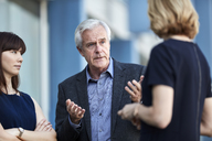 Senior businessman gesturing and talking to colleagues - CAIF13280