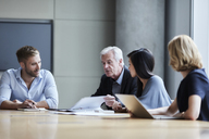 Business people discussing paperwork in conference room - CAIF13283