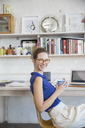 Young woman sitting with mug in home office - CAIF13295
