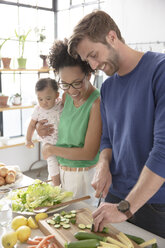 Happy family preparing meal in domestic kitchen - CAIF13298