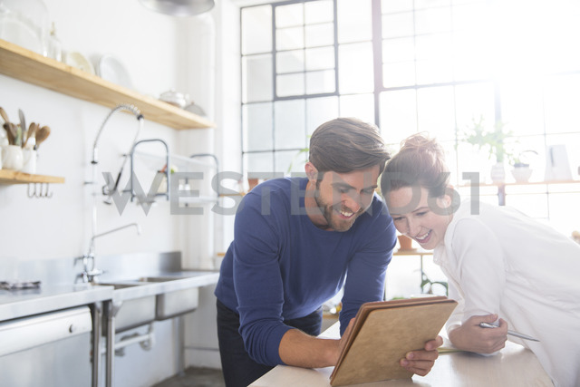 Young couple leaning at kitchen counter and looking at documents - CAIF13301