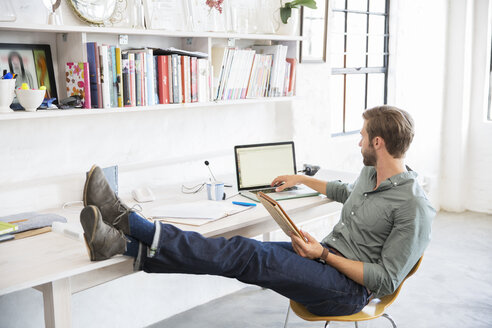 Portrait of young man sitting with legs on desk working with laptop - CAIF13304