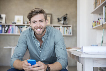 Portrait of young blonde man sitting with mobile phone - CAIF13307